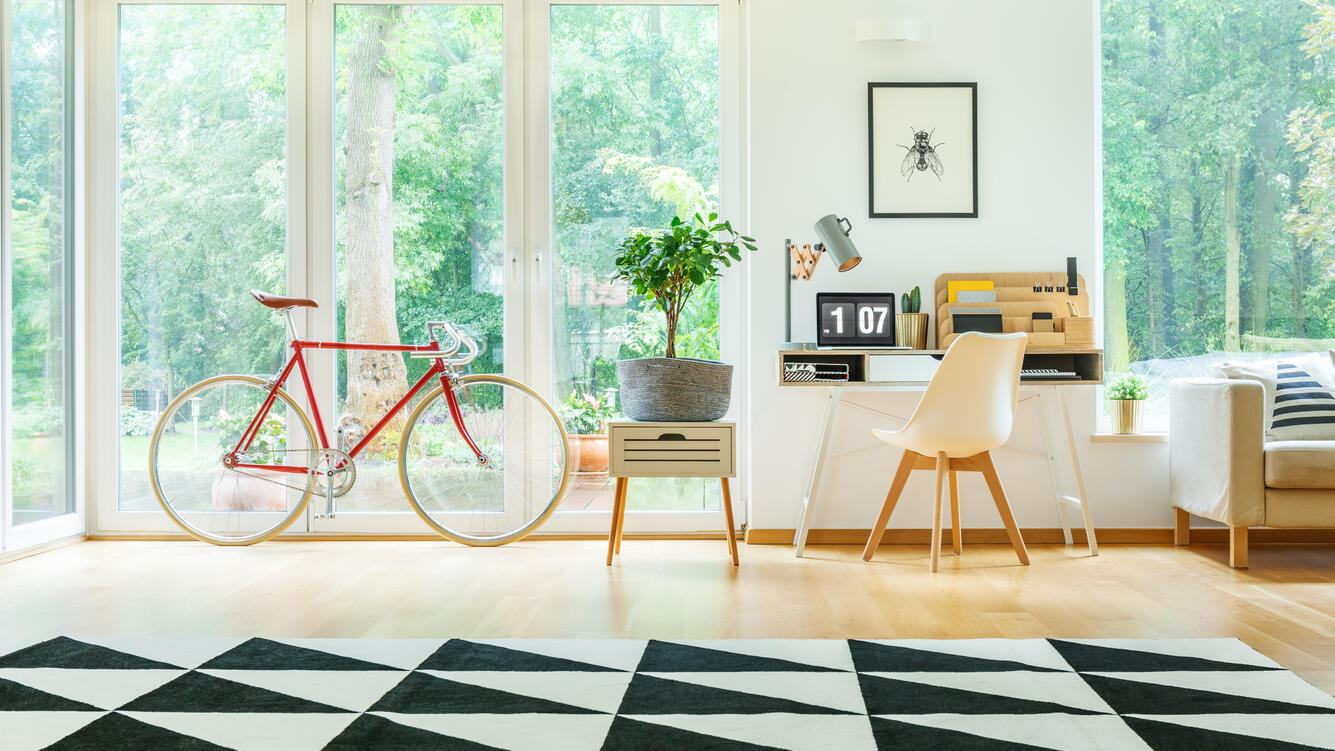 Red bicycle, plant on white cabinet and white chair at desk in spacious living room with geometric carpet