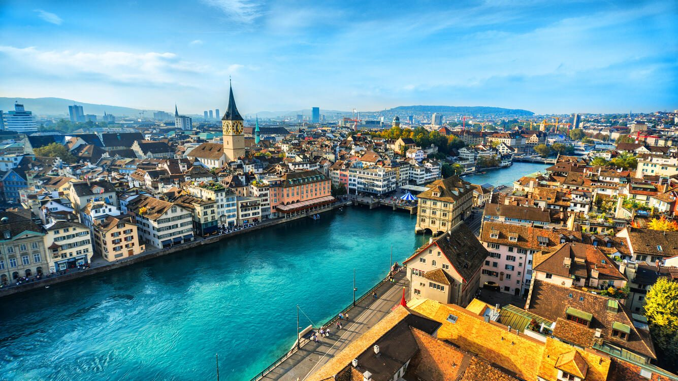 Aerial view of Zurich, Switzerland. Taken from a church tower overlooking the Limmat River. Beautiful blue sky with dramatic cloudscape over the city. Visible are many traditional Swiss houses, bridges and churches.