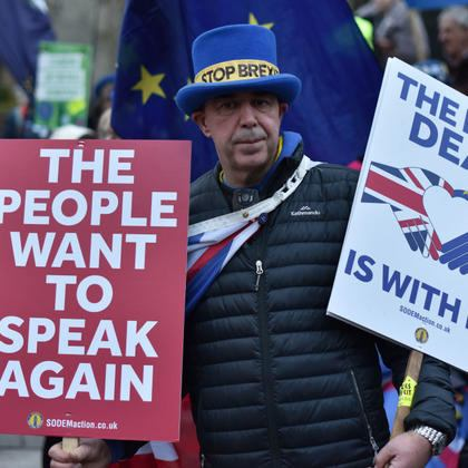 """An anti Brexit protester holds placard saying """"The people want to speak again and The best deal is with the EU"""" outside the Houses of Parliament"""