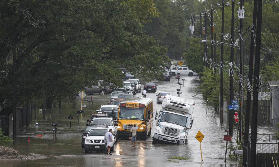 HOUSTON, TX - SEPTEMBER 19: A man tries to direct a school bus on the flooded Hopper Rd. on  September 19, 2019 in Houston, Texas. Gov. Greg Abbott has declared much of Southeast Texas disaster areas after heavy rain and flooding from the remnants of Tropical Depression Imelda dumped more than two feet of water across some areas. (Photo by Thomas B. Shea/Getty Images)
