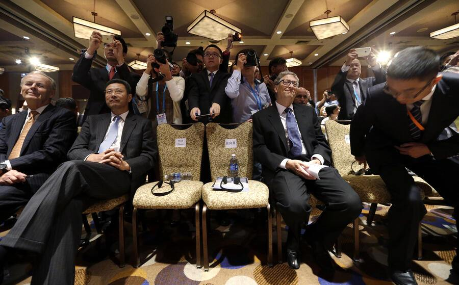 Bill Gates, seated right, co-founder of Microsoft and Chairman of TerraPower, looks on as photographers crowd behind during a signing ceremony linking China National Nuclear Corp. and TerraPower at a U.S. Trade and Investment Cooperation Conference Tuesday, Sept. 22, 2015, in Seattle. The Ministry of Commerce of China (MOFCOM), the State of Washington and partners hosted the conference to explore cooperation between Chinese provinces and U.S. businesses. (AP Photo/Elaine Thompson)