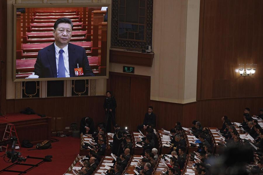 Chinese President Xi Jinping is seen on a big screen as his Premier Li Keqiang delivers the work report at the opening session of the annual National People's Congress at the Great Hall of the People in Beijing, Tuesday, March 5, 2019. China's government announced a robust annual economic growth target and a 7.5 percent rise in military spending Tuesday at a legislative session overshadowed by a tariff war with Washington. (AP Photo/Andy Wong)