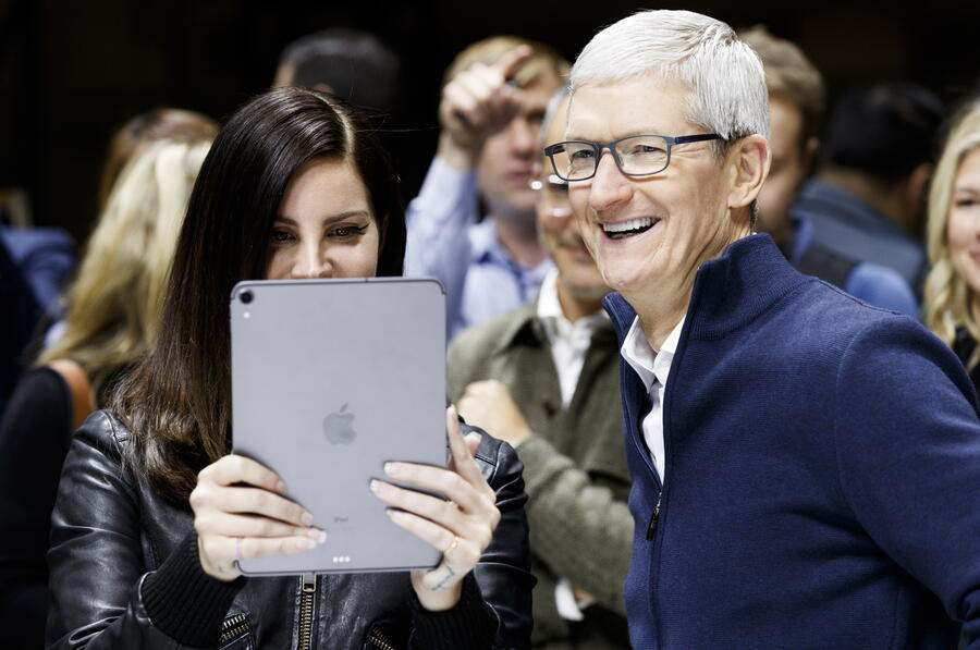 epa07131749 Apple CEO Tim Cook (R) and US singer Lana Del Rey (C) look at a new iPad Pro during an Apple hands-on event in One Hanson Place following a presentation at the Howard Gilman Opera House at the Brooklyn Academy of Music in Brooklyn, New York, USA, 30 October 2018. The event follows soon after a major Apple iPhone product launch in September 2018. EPA/JUSTIN LANE