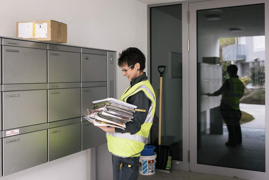 A mail carrier of the Swiss Post drops the post into letterboxes, pictured during a postal delivery tour in Mauensee, Canton of Lucerne, Switzerland, on March 21, 2017. (KEYSTONE/Christian Beutler)