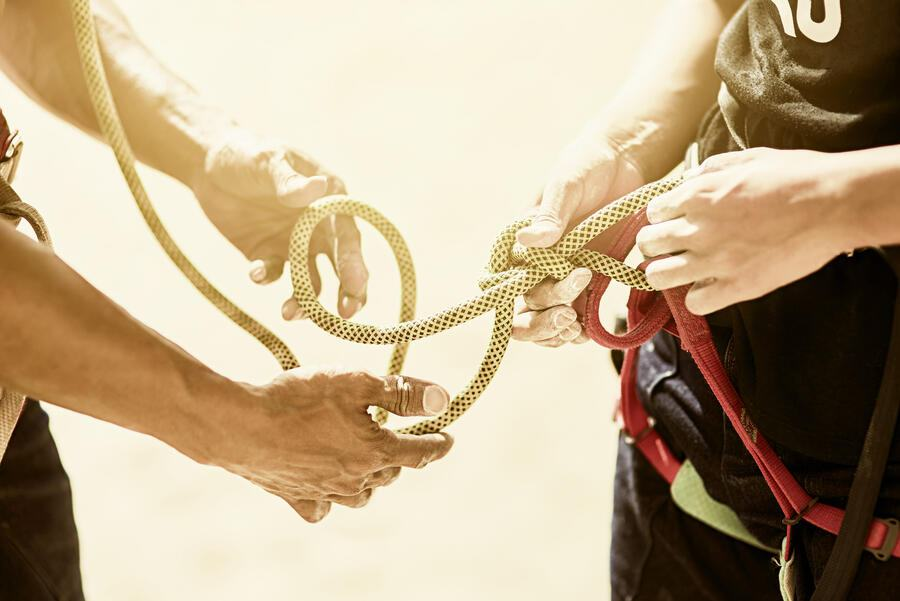 Closeup shot of two rock climbers adjusting their harnesses