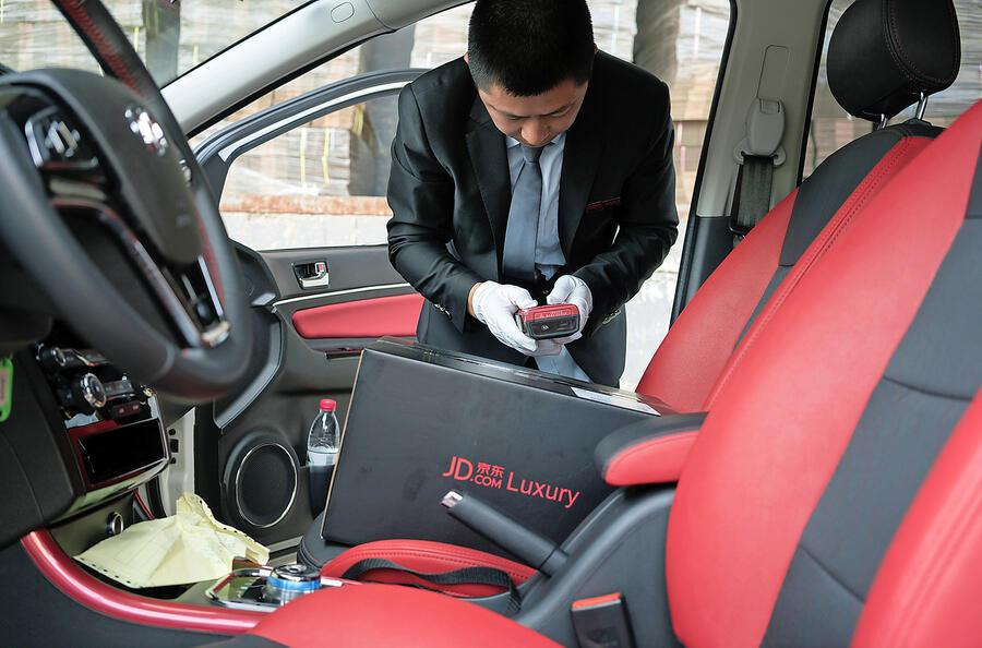 Tang Hongliang, a driver for the JD.com luxury service, gets ready to start the workday in Beijing, June 29, 2017. To court the luxury market, companies like JD.com are using their customer base to offer upscale retailers support on things like white glove deliveries. (Giulia Marchi/The New York Times)