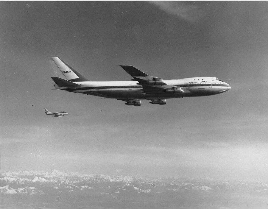 --- ARCHIVE --- VOR 50 JAHREN AM 9. FEBRUAR 1969 STARTET DIE DIE BOEING 747, AUCH JUMBO-JET GENANNT, IHREN ERSTFLUG --- A Boeing model 747, the largest commercial jetliner in the world, flies over the Puget Sound area of western Washington state in Oct. 1969.  The 747 jet is accompanied by a Sabre V chase plane, background, to observe certain flight tests. (KEYSTONE/AP Photo/Str)....
