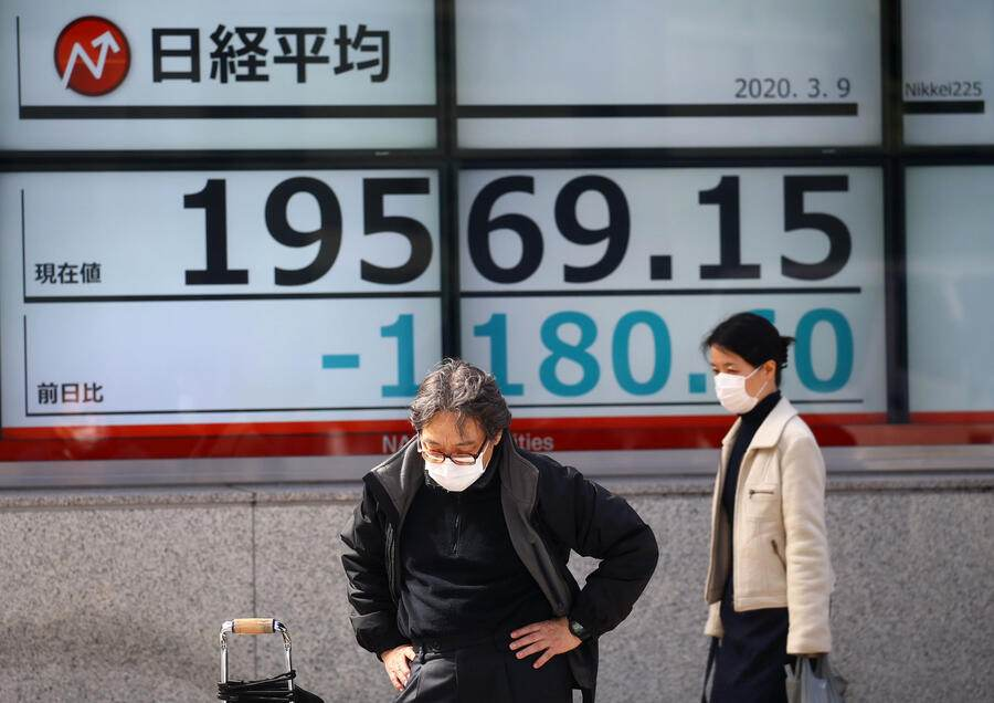 People wearing protective face masks are seen in front of an electronic display showing the Nikkei index outside a brokerage in Tokyo, Japan, following an outbreak of the coronavirus disease (COVID-19), March 9, 2020. REUTERS/Edgard Garrido - RC24GF9C3SXG
