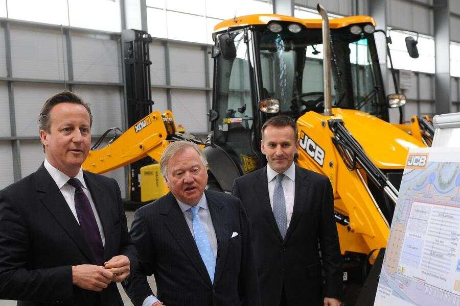 Prime Minister David Cameron is given a tour by Lord Anthony Bamford (centre) and JCB chief executive Graeme Macdonald (right) at the JCB World Logistics site in Newcastle-under-Lyme as part of the Conservative Party's European and Local Election campaign trail.   (Photo by Joe Giddens/PA Images via Getty Images)