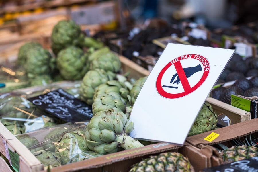 A sign says 'Do not touch' as artichokes lie on a table at the Annecy market on March 20, 2020 in Annecy, France.