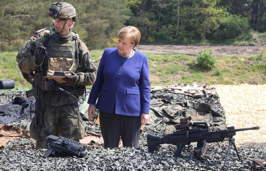 epa07586915 German Chancellor Angela Merkel stands at a gun display during her visit at the NATO Very High Readiness Task Force Land (VJTF L 2019) exercise in Muenster, northen Germany, 20 May 2019. The German Bundeswehr with its Armoured Training Brigade 9 (Panzerlehrbrigade 9) serves as spearhead of the VJTF L in 2019. EPA/FOCKE STRANGMANN