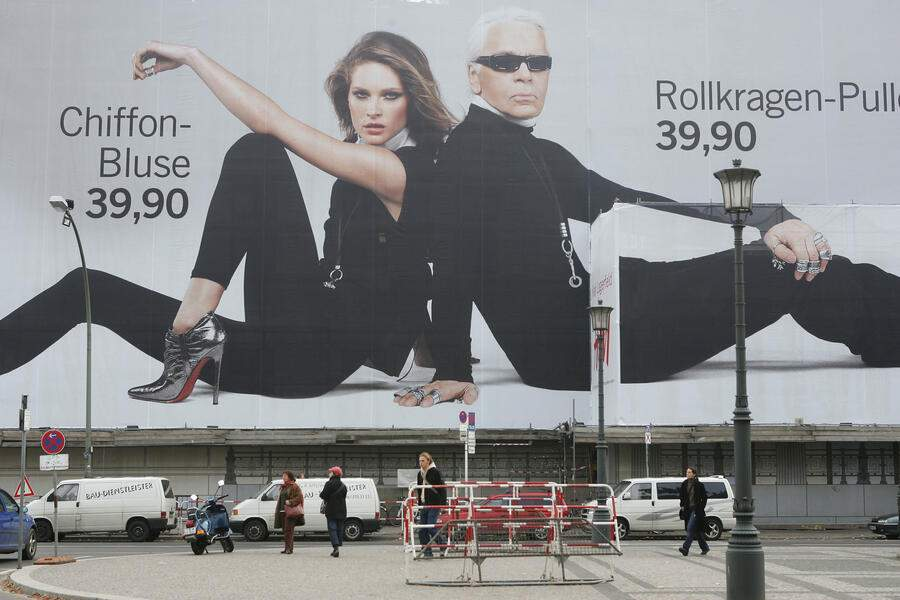 BERLIN - NOVEMBER 3:  A cyclist passes a giant 1,500 square meter advertisement for Swedish fashion retailer H&M that shows German-born fashion designer Karl Lagerfeld and U.S. model Erin Wasson November 3, 2004 in central Berlin, Germany. The Karl Lagerfeld collection goes on sale starting November 12, 2004 at selected H&M stores.  (Photo by Sean Gallup/Getty Images)