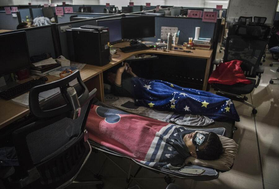 Huawei employees sleep at their cubicle during their lunch break, which is known to be common practice in many workplaces in China, at the research and development area in the Bantian campus on April 12, 2019, in Shenzhen, China.
