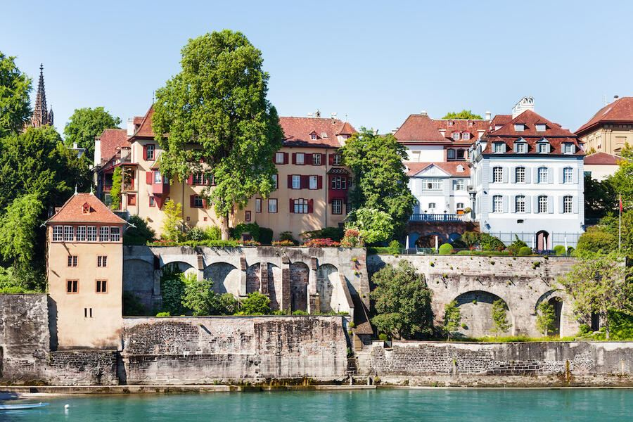 Beautiful view of Basel waterfront with stone fortification and medieval houses at sunny day, Switzerland