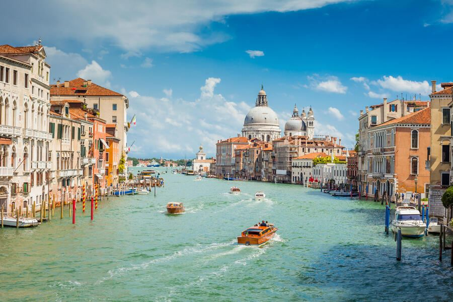 An iconic view from Accademia Bridge (Italian: Ponte dell'Accademia) in Venice. Numerous boats and vessels are seen cruising along the Grand Canal on a bright sunny day. Santa Maria Della Salute is seen in background.