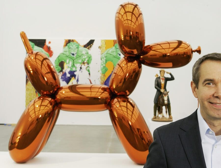 "FILE - In this Thursday, May 29, 2008 file photo, artist Jeff Koons poses beside one of his works, ""Balloon Dog,"" on display at Chicago's Museum of Contemporary Art. The more than 10-foot-high chromium stainless steel sculpture of a balloon-animal dog has an orange metallic coating and is part of an exhibit of about 60 other sculptures and paintings by Koons. (AP Photo/Charles Rex Arbogast)"