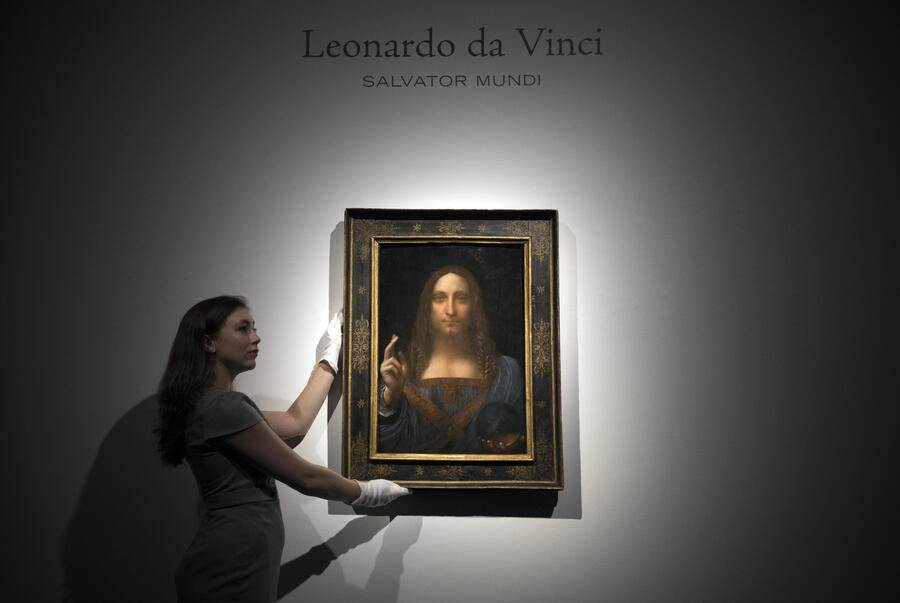 LONDON, ENGLAND - OCTOBER 24:  A member of staff poses with a painting by Leonardo da Vinci entitled 'Salvator Mundi' before it is auctioned in New York on November 15, at Christies on October 24, 2017 in London, England. The painting is the last Da Vinci in private hands and is expected to fetch around 100,000,000 USD.  (Photo by Carl Court/Getty Images)