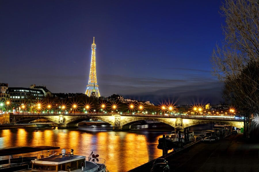 Eiffel Tower, Pont des Invalides and Seine River bank in Paris at night seen from Pont Alexandre III.