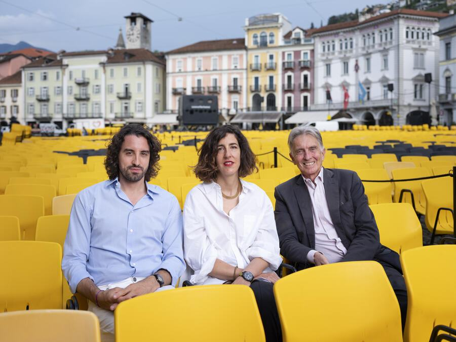 Raphael Brunschwig, Chief Operating Officer, Lili Hinstin, Artistic Director, and Marco Solari, President of the Locarno Film Festival, from left to right, pose for a photograph on the Piazza Grande in Locarno, Switzerland, on August 5, 2019. (KEYSTONE/Christian Beutler)