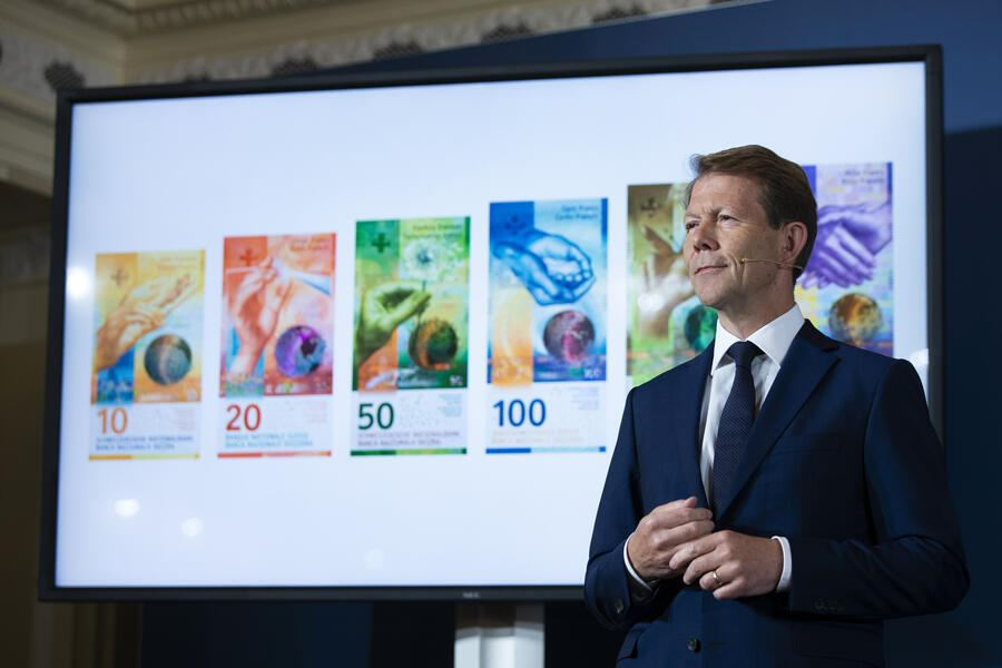 Fritz Zurbruegg, Vice president of the Swiss National Bank, stands beside a screen showing the new series of Swiss banknotes during the presentation of the new Swiss 100 francs banknote in Bern, Switzerland, Tuesday, September 3, 2019. (KEYSTONE/Peter Klaunzer)