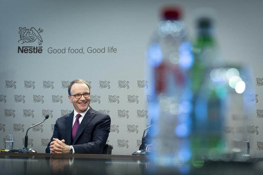 Nestle's CEO Ulf Mark Schneider smiles next to bottles of water during the 2019 full-year results press conference of the food and drinks giant Nestle, in Vevey, Switzerland, Thursday, February 13, 2020. (KEYSTONE/Laurent Gillieron)