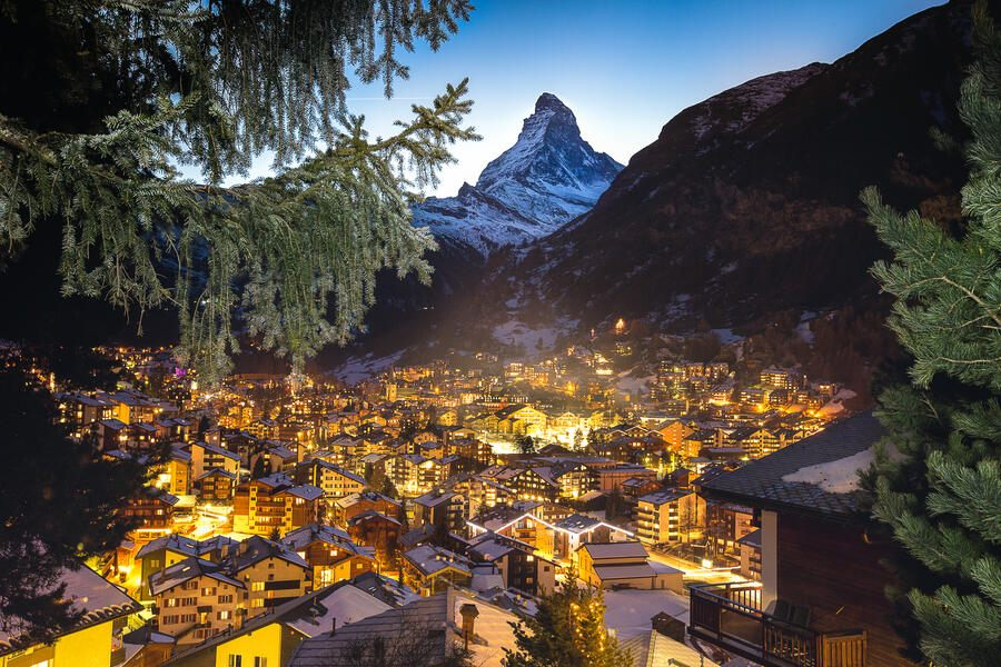 Warm window lights from the swiss alpine village of Zermatt light the valley at twilight with the Matterhorn peak above it