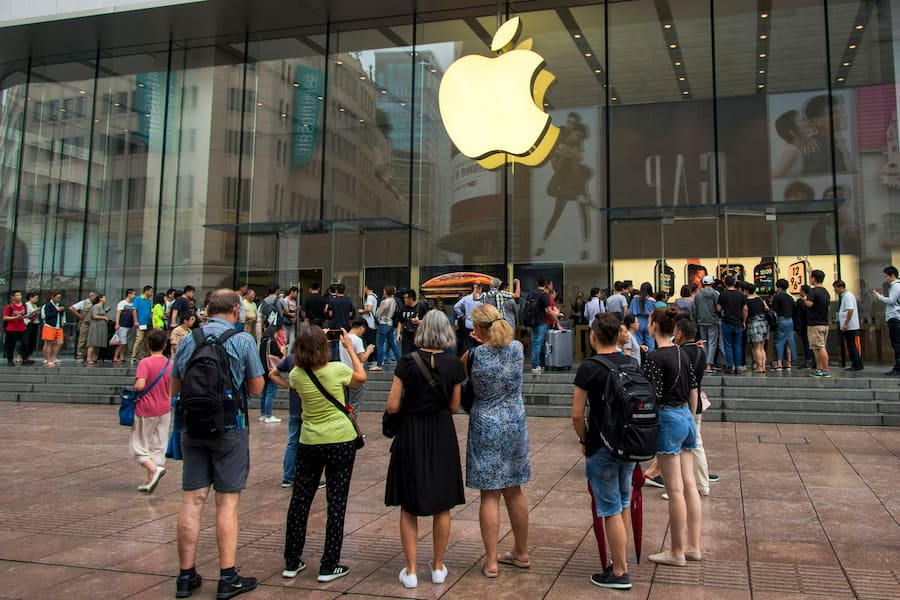 In this Friday, Sept. 21, 2018, photo, foreign tourists watch people queue in line to enter the Apple Store for the debut of the latest iPhones in Shanghai. China imposed new tariff hikes on U.S. goods on Monday, Sept. 24, 2018, and accused Washington of bullying, giving no sign of compromise in an intensifying battle over technology that is weighing on global economic growth. (Chinatopix via AP) (KEYSTONE/AP CHINATOPIX/)