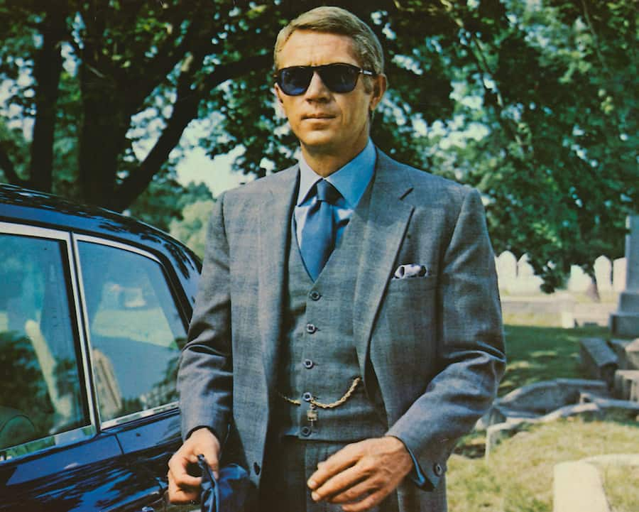 Steve McQueen (1930-1980), US actor, wearing sunglasses with a grey suit, a blue shirt and dark blue tie in a publicity image issued for the film, 'The Thomas Crown Affair', USA, 1968. The crime drama, directed by Norman Jewison, starred McQueen as 'Thomas Crown'. (Photo by Silver Screen Collection/Getty Images)